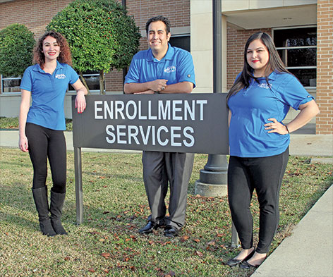 Staff near Enrollment Services sign