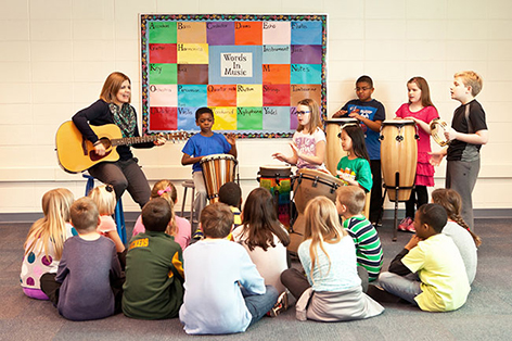 Teacher and K-12 students playing instruments.