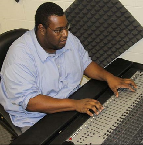 Man adjusting settings on sound board