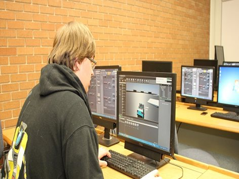 Student working at computer, using a graphics design program.